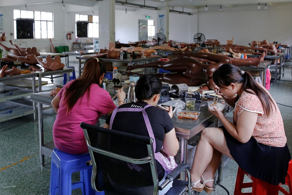 Workers take a break for lunch on the factory floor. They produce around 2,000 dolls a month
