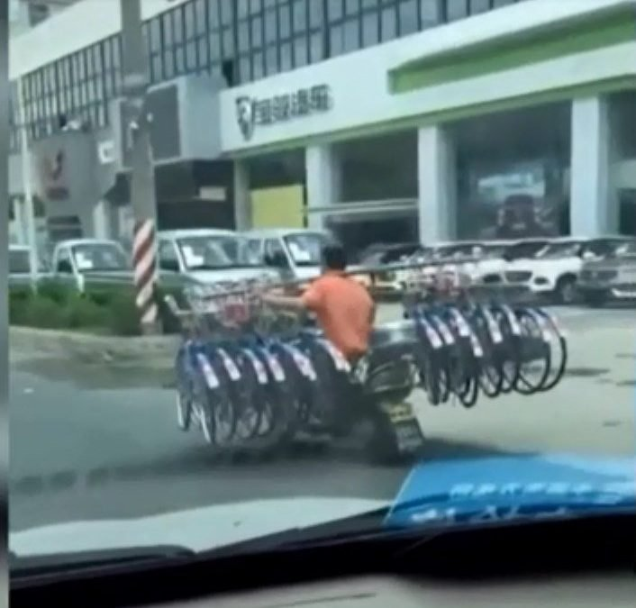 """Video: The man carrying 16 bikes on shoulder while driving motorbike down road causes """"shock"""""""