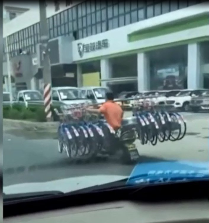 The man carrying 16 bikes on shoulder while driving motorbike down road causes