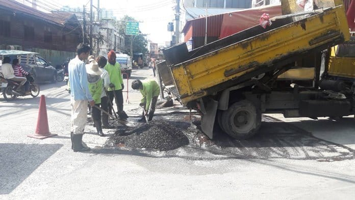 Potholes patched at Amorn Market. Workers patched potholes outside