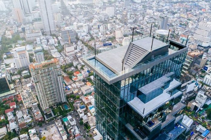 Tourists posing on Bangkok's new observation deck. Daring tourists have headed high above Bangkok's skyline to the city's new observation