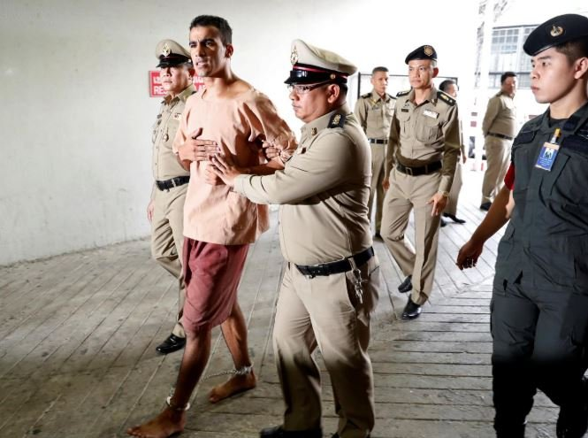 Feet shackled, Bahraini footballer arrives at Thai court to fight extradition