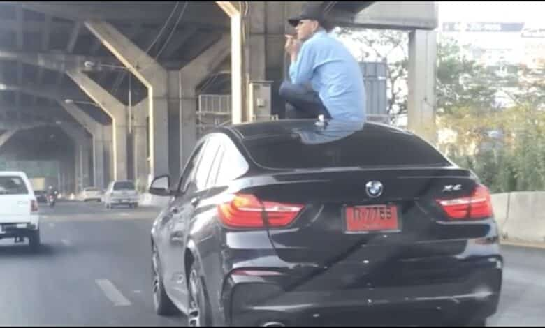 Driver Sits On Car Roof After Crash. This is the bizarre moment a BMW driver sat on the roof of his car smoking a cigarette after causing