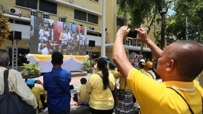 People brave the heat to watch broadcast of Royal Coronation. At 2 pm on Saturday, many loyal subjects remained seated on sidewalks in front of the Grand