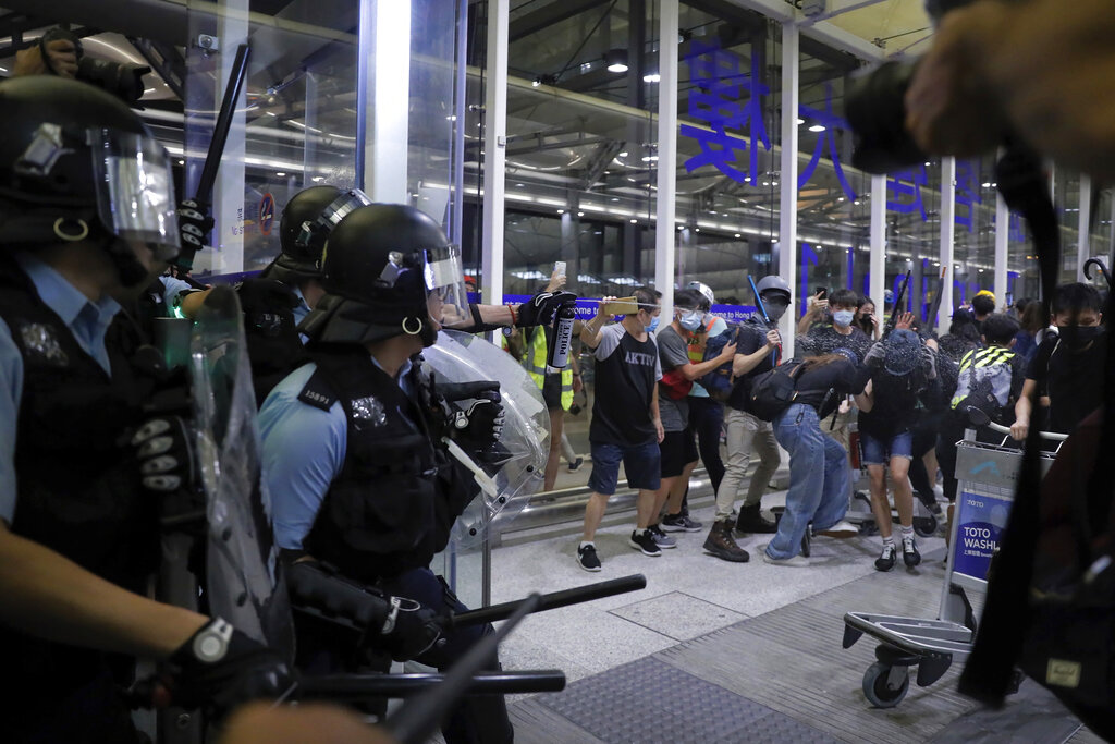 Policemen in riot gears use pepper spray on the protesters during a demonstration at the Airport in Hong Kong, Tuesday, Aug. 13, 2019. Chaos has broken out at Hong Kong's airport as riot police moved into the terminal to confront protesters who shut down operations at the busy transport hub for two straight days. Photo: Kin Cheung / AP