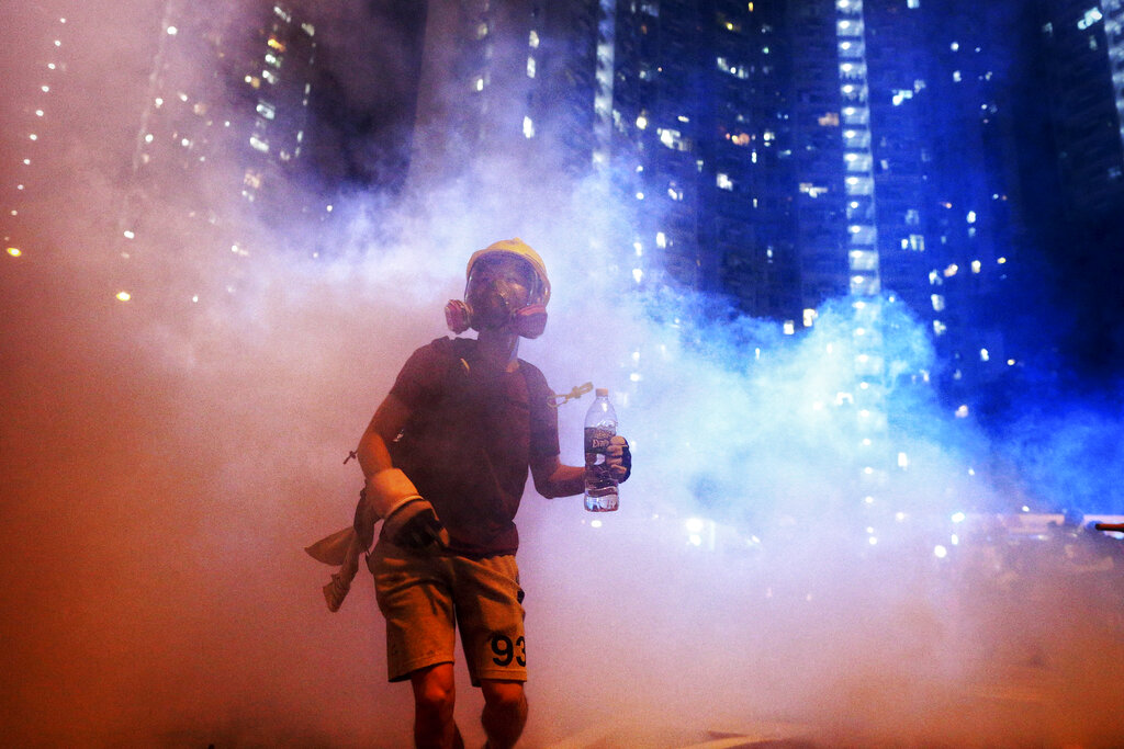 A protester stands in the midst of tear gas during confrontation with police in Hong Kong during the early hours of Sunday, Aug. 4, 2019. Hong Kong protesters ignored police warnings and streamed past the designated endpoint for a rally Saturday in the latest of a series of demonstrations targeting the government of the semi-autonomous Chinese territory. Photo: Elson Li / HK01 via AP