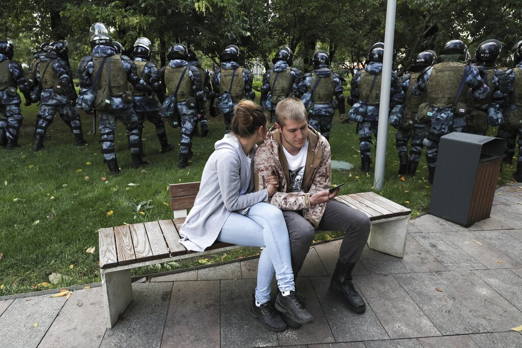A couple sit in a boulevard as police walk to prevent protesters during a rally in Moscow, Russia, Saturday, Aug. 10, 2019. Tens of thousands of people rallied in central Moscow for the third consecutive weekend to protest the exclusion of opposition and independent candidates from the Russian capital's city council ballot. Photo: AP
