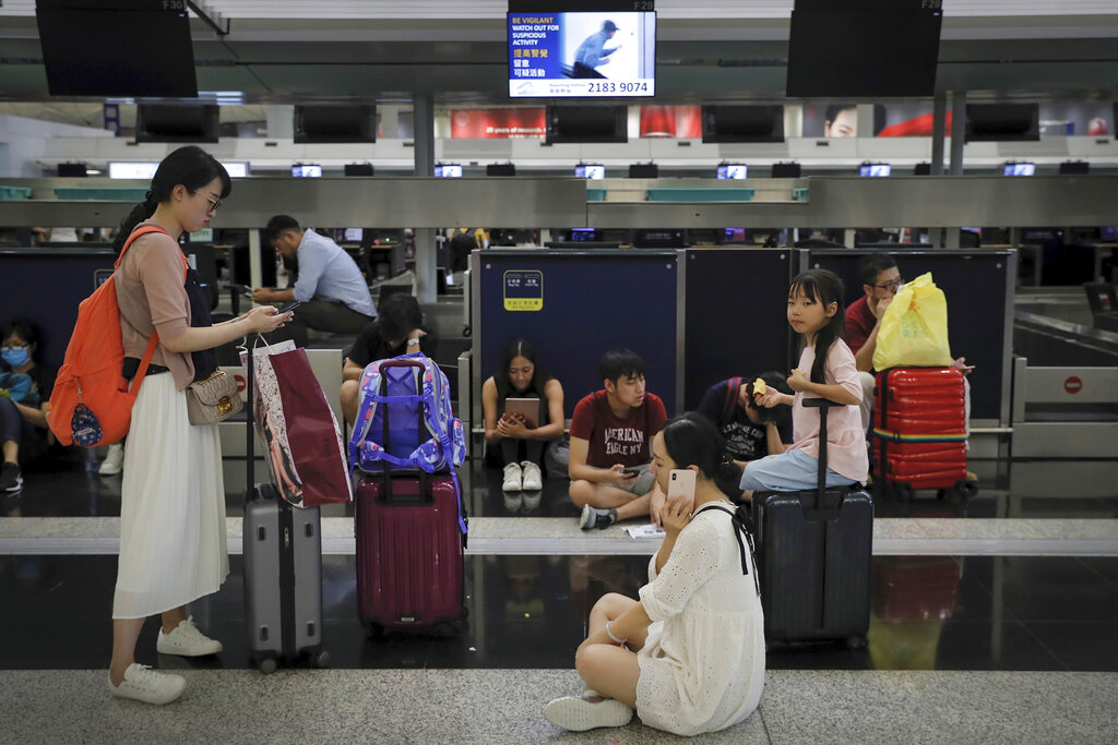 Travelers gather at the closed check-in counters as protesters stage a protest at the Hong Kong International Airport, Monday, Aug. 12, 2019. Photo: Kin Cheung / AP