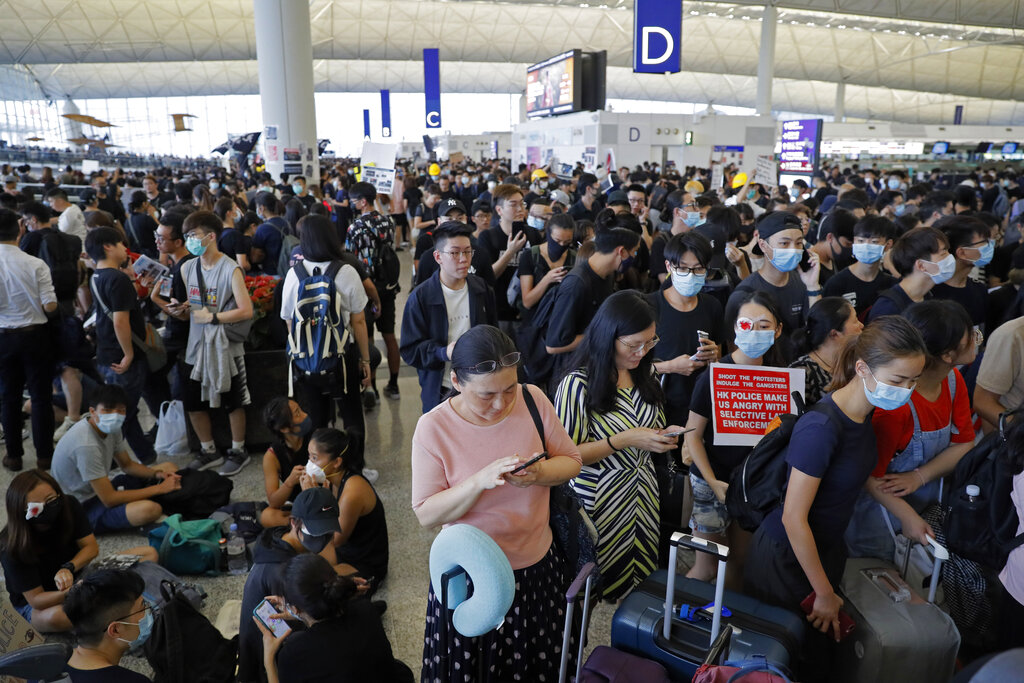 Stranded travelers using smartphones are surrounded by protesters during a protest at the Hong Kong International Airport, Monday, Aug. 12, 2019. Photo: Kin Cheung / AP