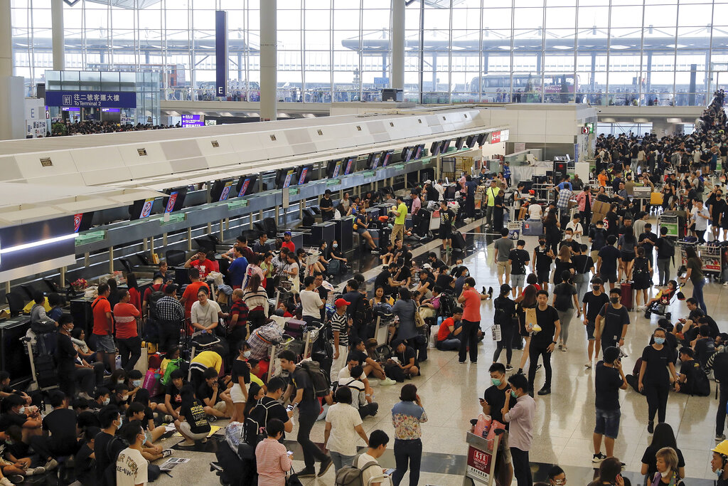 Protesters gather near the stranded travelers at the closed check-in counters during a protest at the Hong Kong International Airport, Monday, Aug. 12, 2019. Photo: Kin Cheung / AP