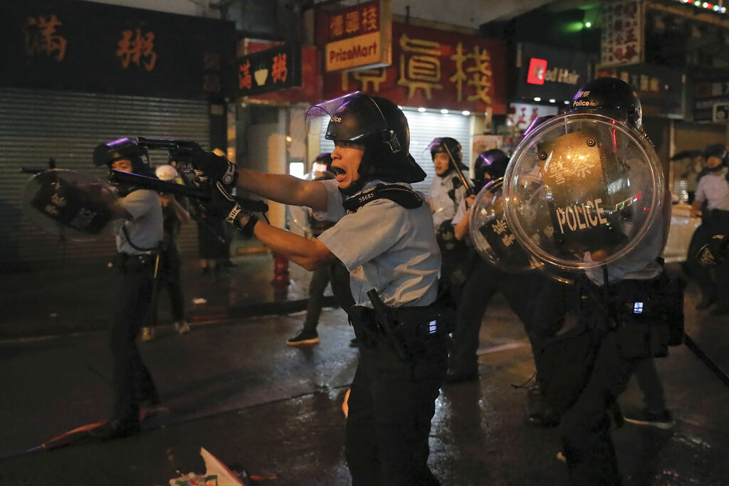 Policemen pull out their guns after a confrontation with demonstrators during a protest in Hong Kong, Sunday, Aug. 25, 2019. Hong Kong police have rolled out water cannon trucks for the first time in this summer's pro-democracy protests. The two trucks moved forward with riot officers Sunday evening as they pushed protesters back along a street in the outlying Tsuen Wan district. Photo: Vincent Yu / AP