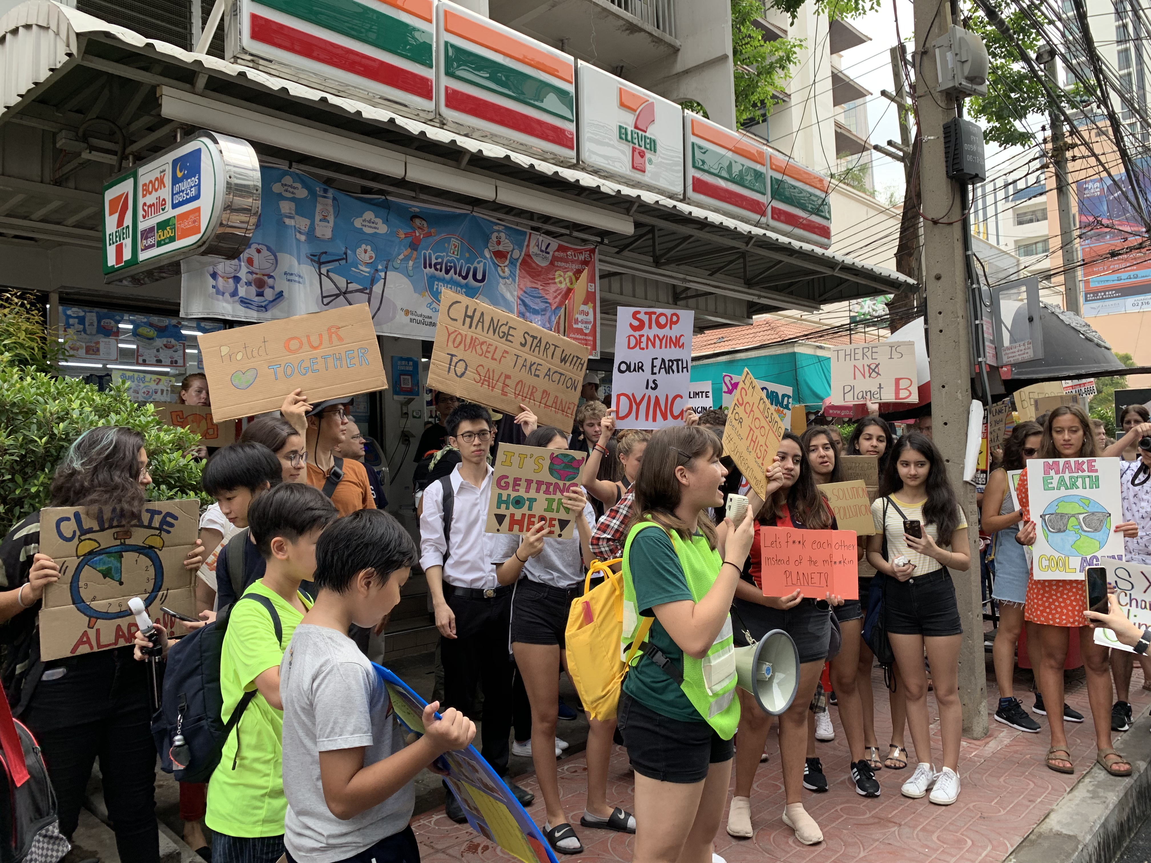 Marlena Wilson speaking in front of a 7-Eleven store on Phahonyothin Soi 7.