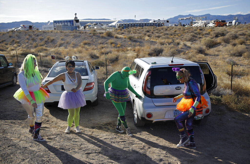"""From left, Alex Clark, Carolyn Milner, Audrie Clark and Lucinda Clark dance near their car outside of the Storm Area 51 Basecamp event Friday, Sept. 20, 2019, in Hiko, Nev. The event was inspired by the """"Storm Area 51"""" internet hoax. Photo: John Locher / AP"""