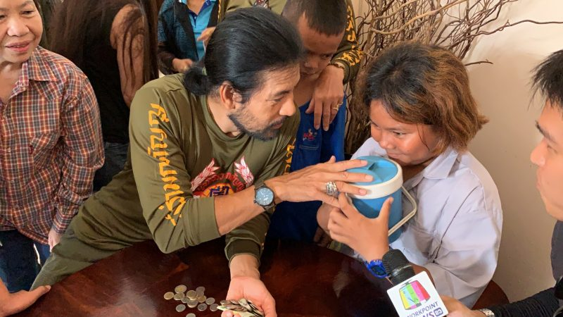 Bin Banluerit accepts a donation of 321 baht from Supatchara Kemnangrong, 11, on Sept. 19, 2019, which she had collected in her piggy bank for him.