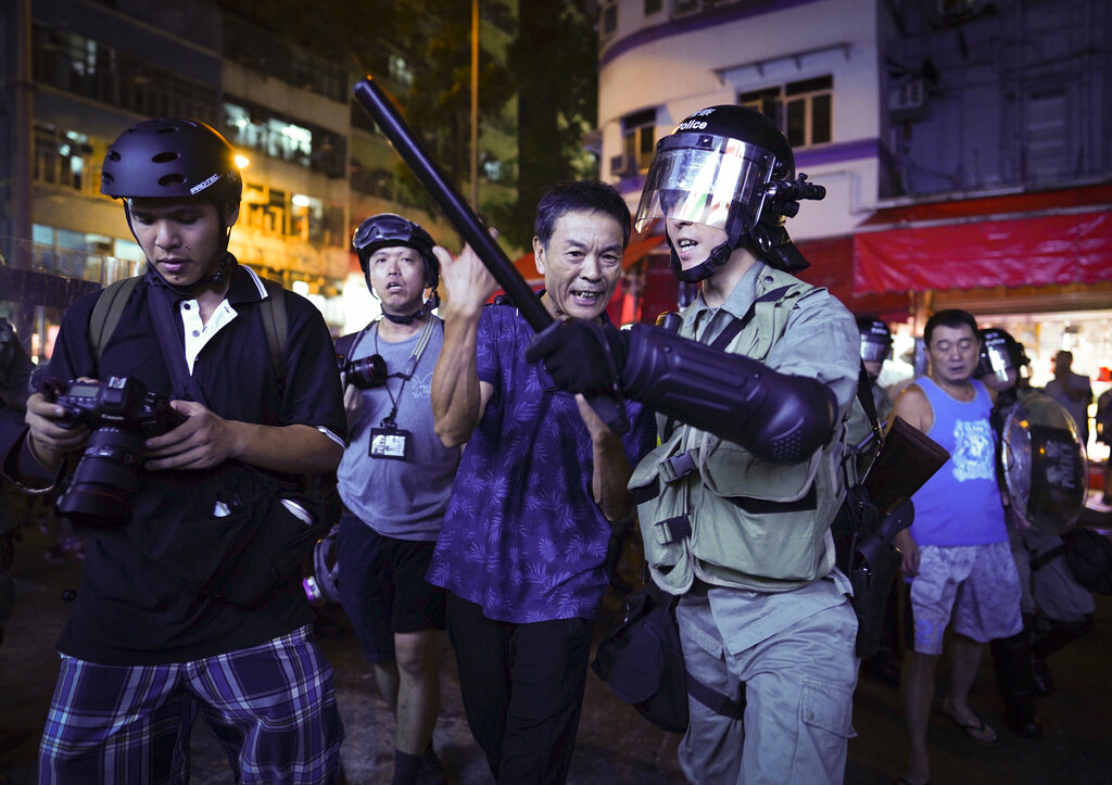 A Pro-China supporter, center, is escorted by police after confronting journalists in north point, Hong Kong, Sunday, Sept. 15, 2019. Police fired a water cannon and tear gas at protesters who lobbed Molotov cocktails outside the Hong Kong government office complex Sunday, as violence flared anew after thousands of pro-democracy supporters marched through downtown in defiance of a police ban. Photo: Vincent Yu / AP
