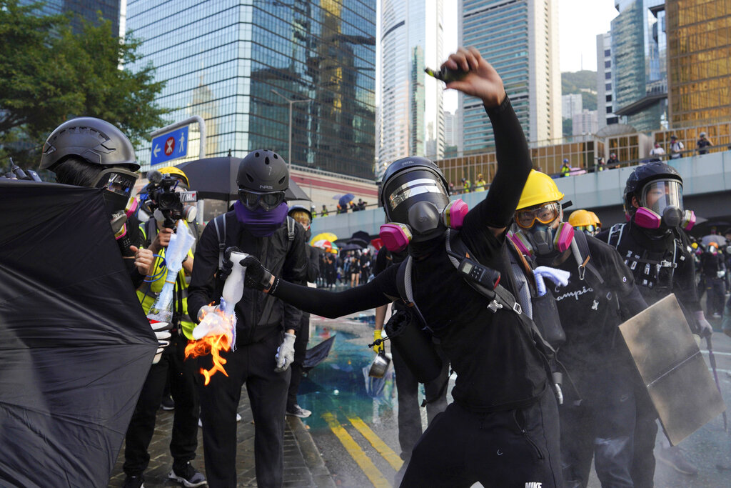 An anti-government protester throws a Molotov cocktail during a demonstration near Central Government Complex in Hong Kong, Sunday, Sept. 15, 2019. Police fired a water cannon and tear gas at protesters who lobbed Molotov cocktails outside the Hong Kong government office complex Sunday, as violence flared anew after thousands of pro-democracy supporters marched through downtown in defiance of a police ban. Photo: Vincent Yu / AP