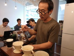 Piyachat making a cup of drip coffee.